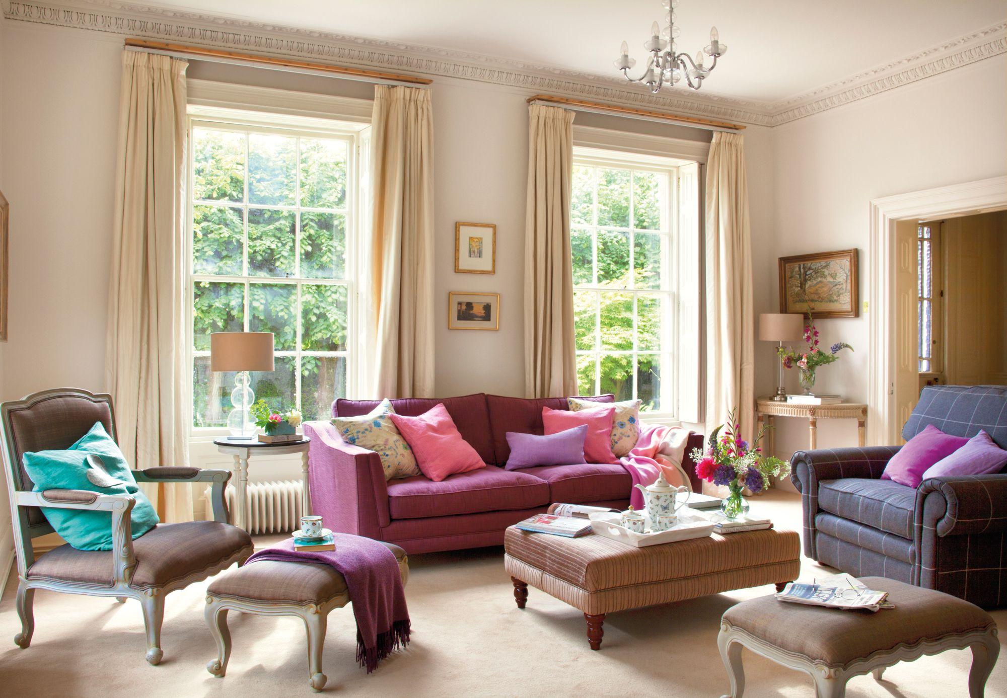 Sofá morado con cojines en tonos rosa, malva y violeta en salón de ...
