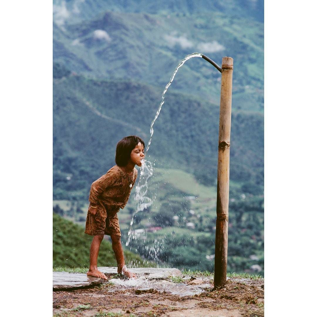 Photo by @stevemccurryofficial // A child drinks water from a flowing artesian well in rural Nepal. Despite the abundance of water resources in the country much of it is contaminated. Artesian tubewell water is much safer than ground water. by natgeo