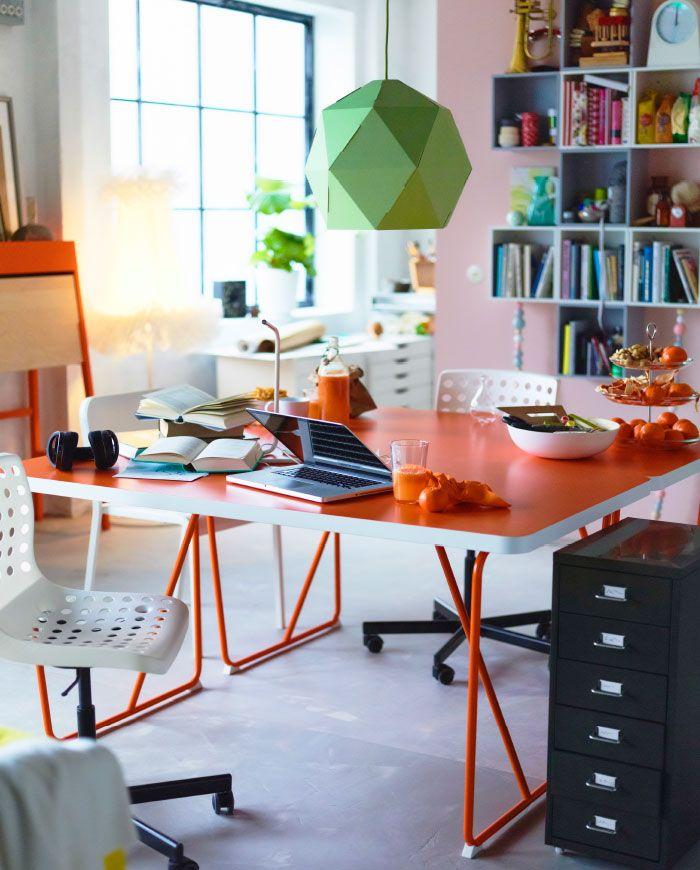 Studio-asunto, jossa kaksi oranssia pöytää vierekkäin.