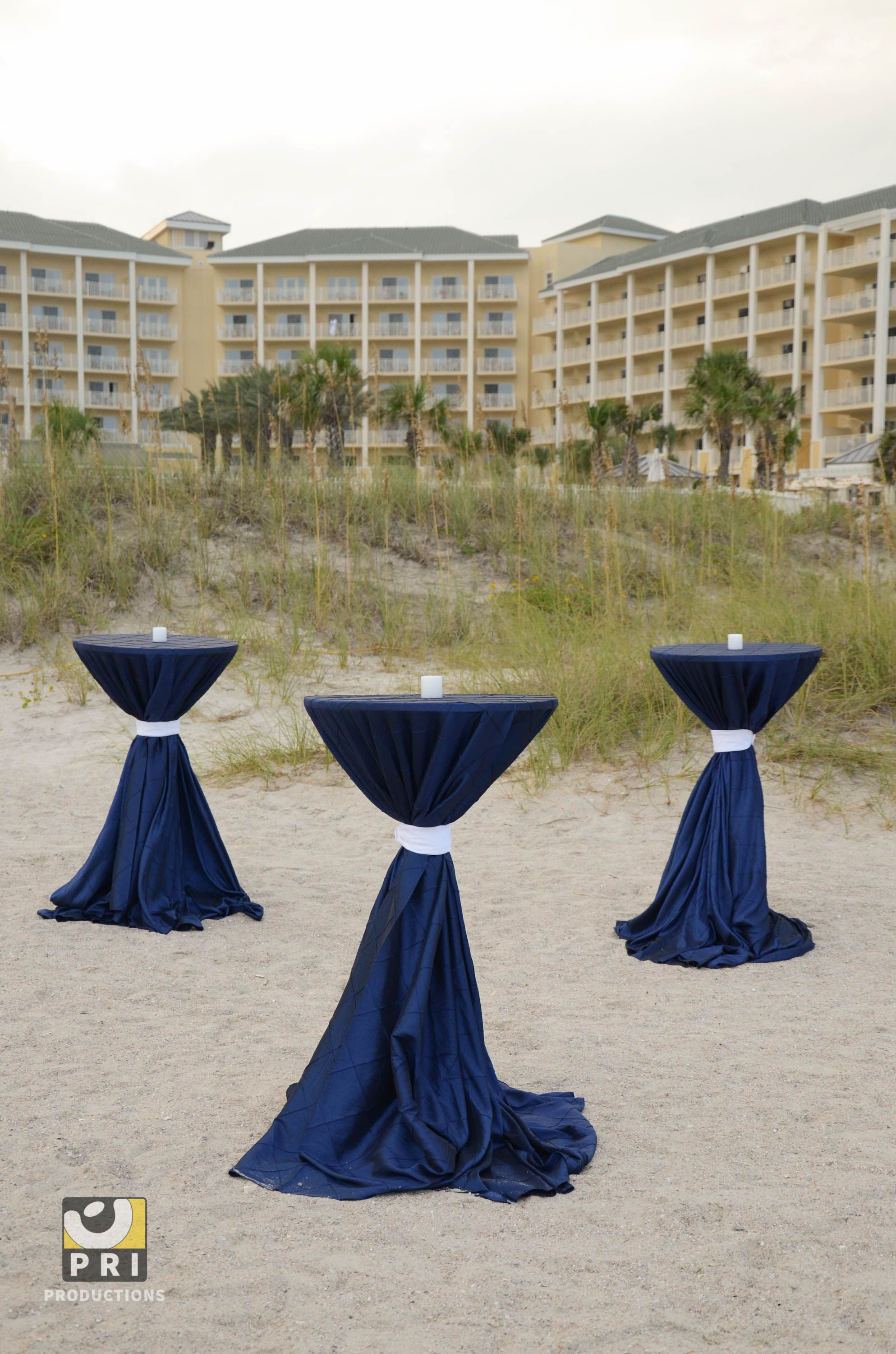 Highboy Cocktail Tables With Blue Linens And Candles On