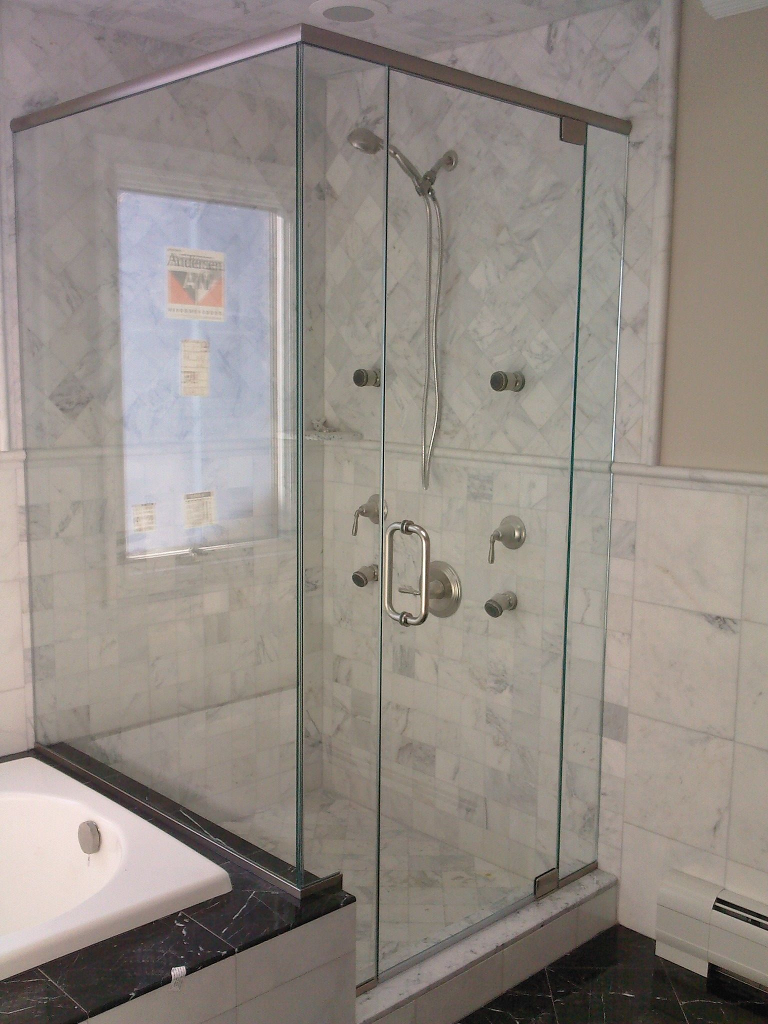 Marble tile patterns and glass shower wall on edge of tub surround ...