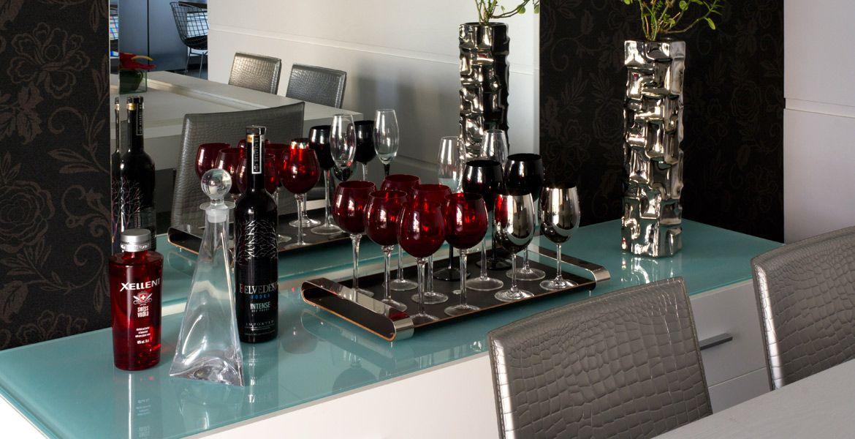 Projetada pelo arquiteto Léo Shetman, a sala de jantar ganhou um bar que funciona como buffet e apoio. Todo branco e com tampo em vidro de tom esverdeado, o móvel compõe perfeitamente com o restante do ambiente. O espelho dá um toque de sofisticação ao espaço.