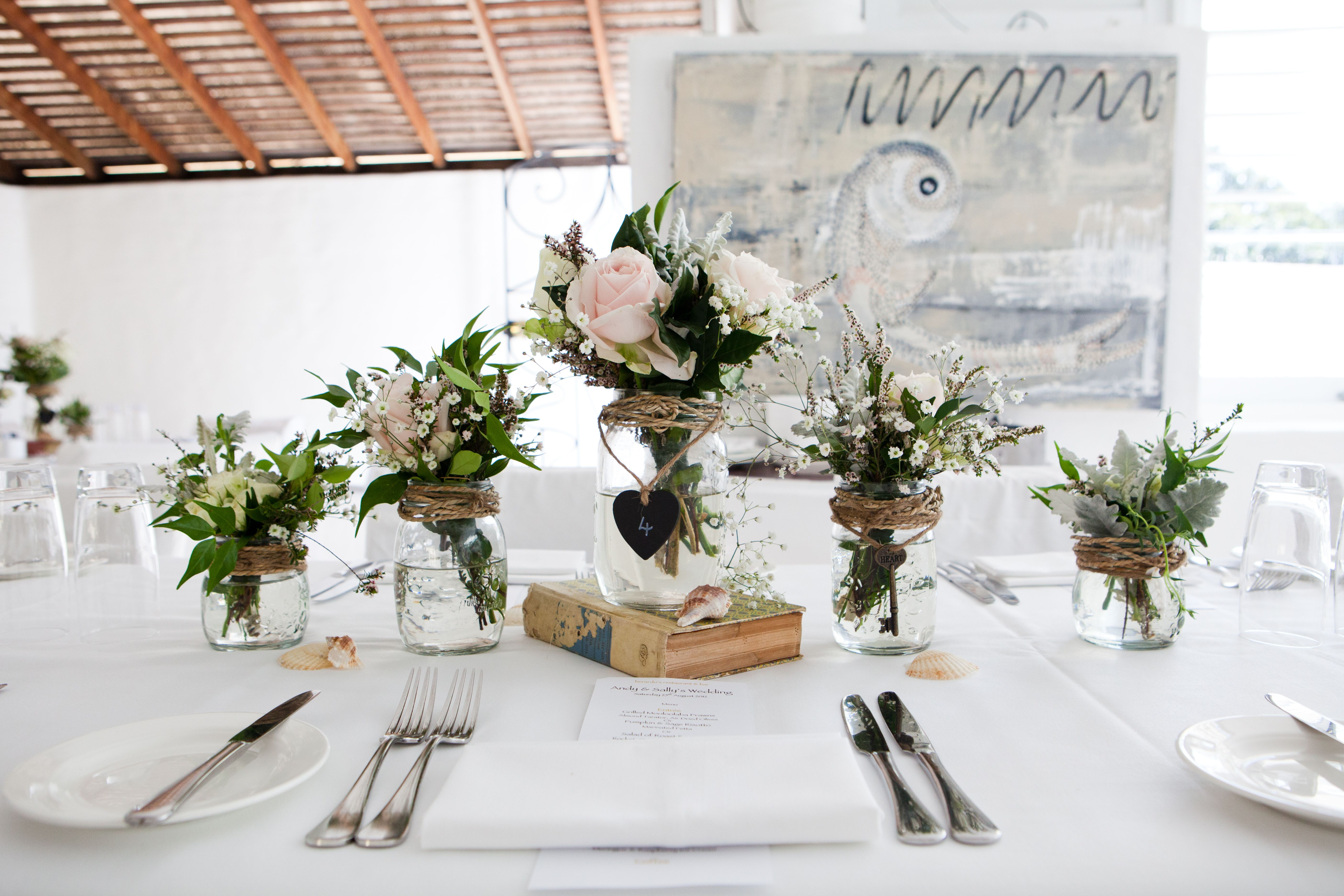 Simplistic centrepieces using vintage books, glass jars and soft ...