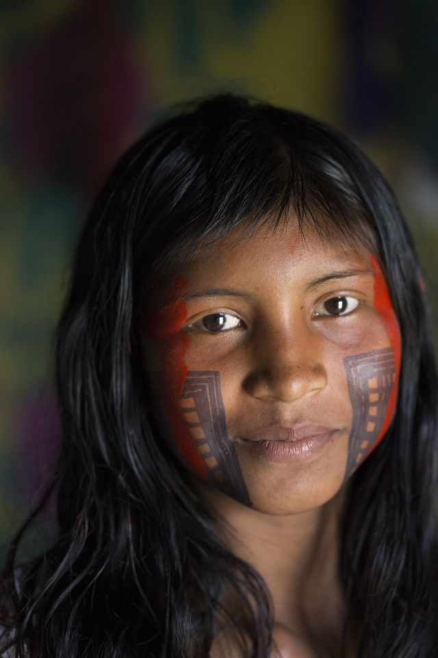 An elaborately painted young Xikrin woman poses for a portrait in her home in the Brazilian Amazon.