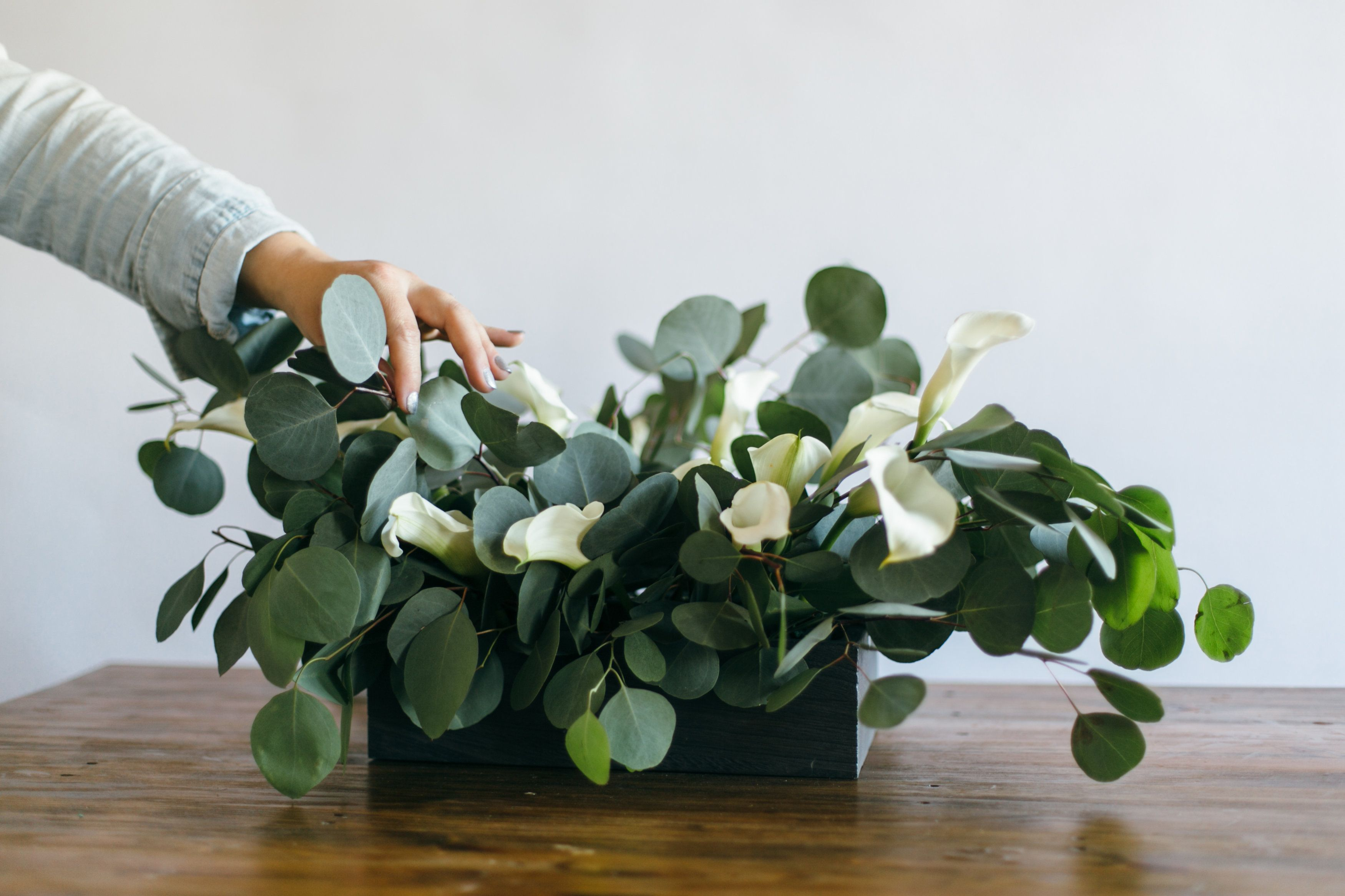 How to DIY a minimal wedding table centerpiece with maximum impact from only two floral ingredients: Eucalyptus & Calla Lilies.