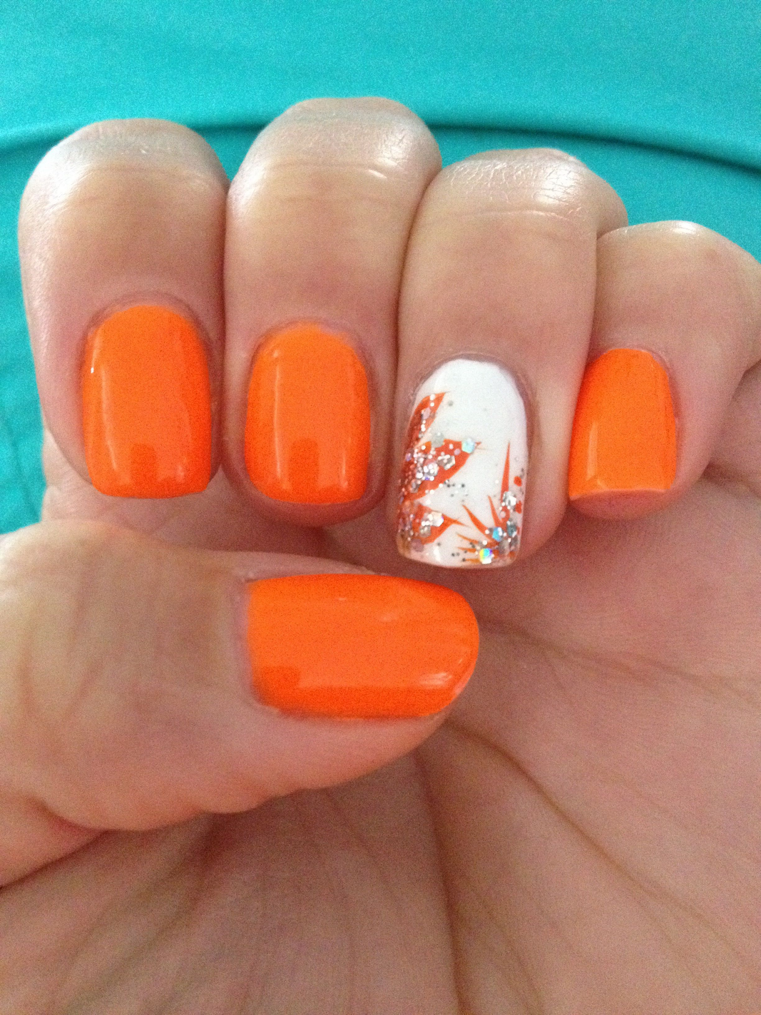 Orange Nails with White Accent Applying the Orange Strokes with a Striper - Add in some glitter, or dots, or pretty much what you would like.