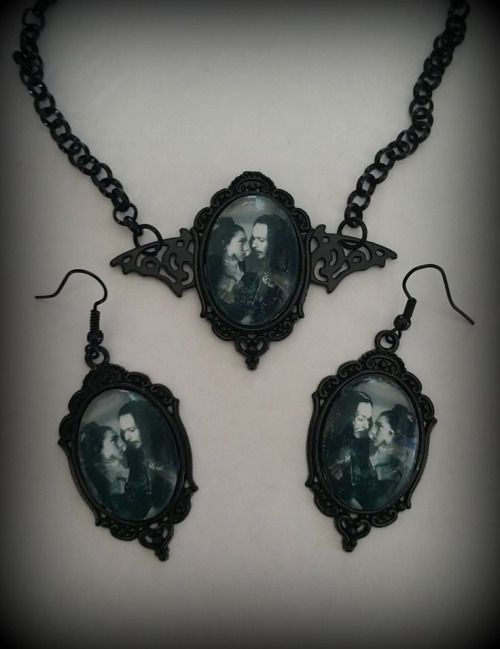 An ornate cameo in gloss black, with a filigree bat pendant set behind. A glass dome sits in the frame, and contains an image of Count Vlad and Mina from Dracula.The pendant is worn on an 18 inch nickel free gloss black rolo chain.The earrings are worn on nickel free black ear hooks.Glass size 1 inch tall.   Trovato su curiology.bigcartel.com