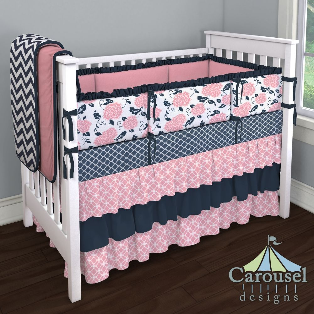 Crib bedding in Coral Pink Sunburst, Solid Navy, Watermelon Minky, White and Navy Zig Zag, Coral Pink and Navy Floral, Solid Navy Minky, Navy Quatrefoil. Created using the Nursery Designer® by Carousel Designs where you mix and match from hundreds of fabrics to create your own unique baby bedding. #carouseldesigns
