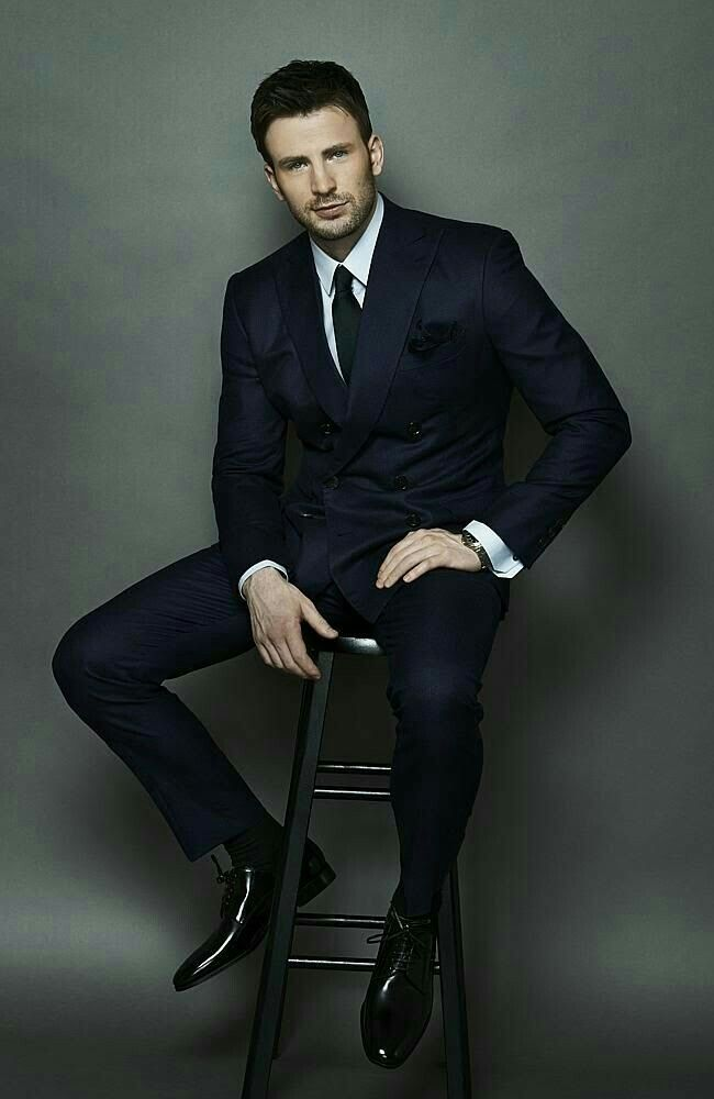 Chris Evans in a black suit with white shirt, black tie, and black shoes.