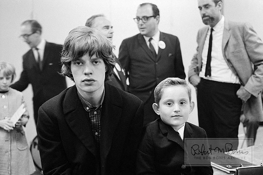 "A few days into their second US tour, Mick Jagger obliges a young fan with a backstage photo op during the taping of the T.A.M.I. Show ""filmed in Electronovision"" (video transferred to film) at the Santa Monica Civic Auditorium in Santa Monica, California."