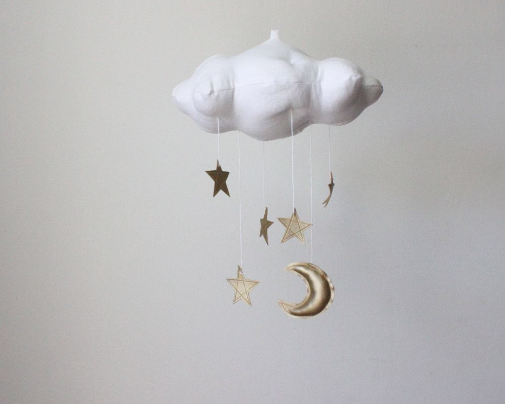 Laying beneath this celestial cloud is sure to inspire a future dreamer. This handmade cloud mobile is scattered with golden stars and sliver moon to delight your little dreamer. The perfect touch for