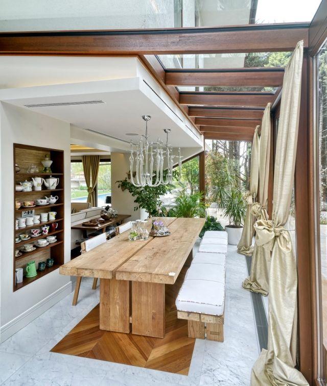 une table en bois massif et des bancs en bois avec des coussins