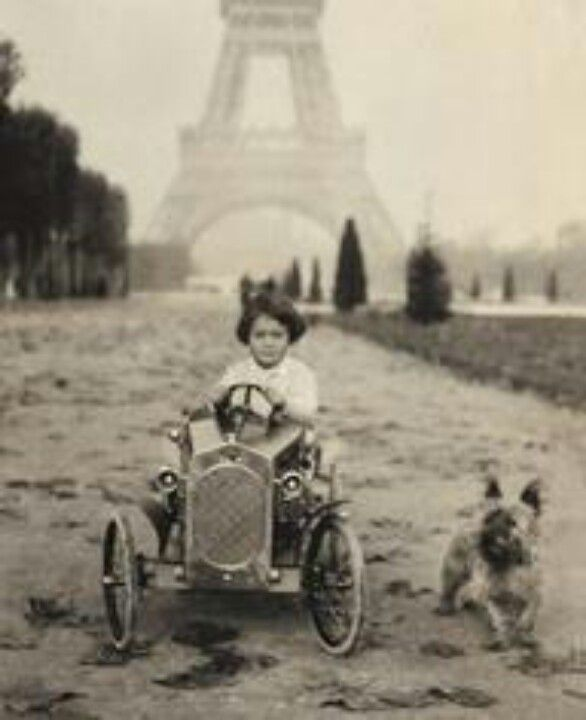 Eiffel Tower background, kid in riding toy with Cairn Terrier