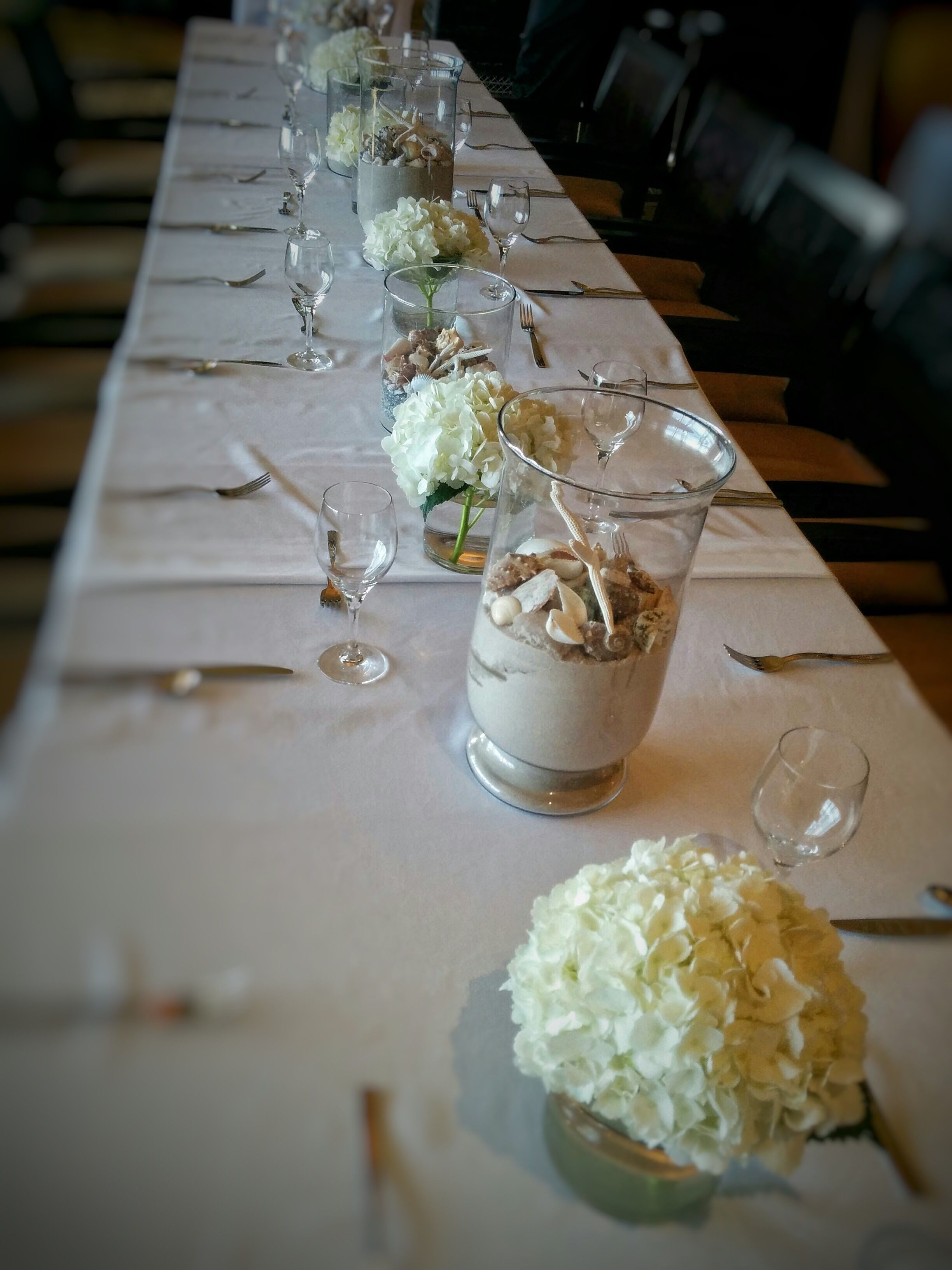 Long table with white hydrangeas shell centerpieces