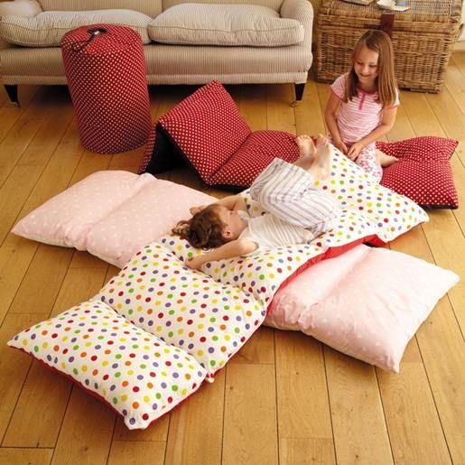 Eine Mutter legt vier Kissen auf den Boden für eine GENIALE Kreation ...
