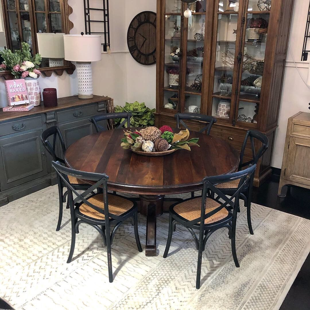 A Classic Round Dining Table Surrounded By Distressed X Back