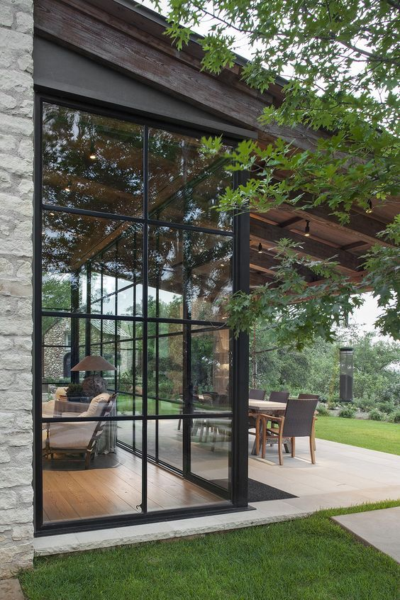 Oh my! These black full height windows paired with the stone ...