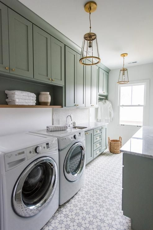 Well appointed gray green laundry room is equipped with a white front loading washer and dryer placed on white and gray cement floor tiles beneath a wood shelf fixed under gray green upper cabinets complemented with brass knobs.