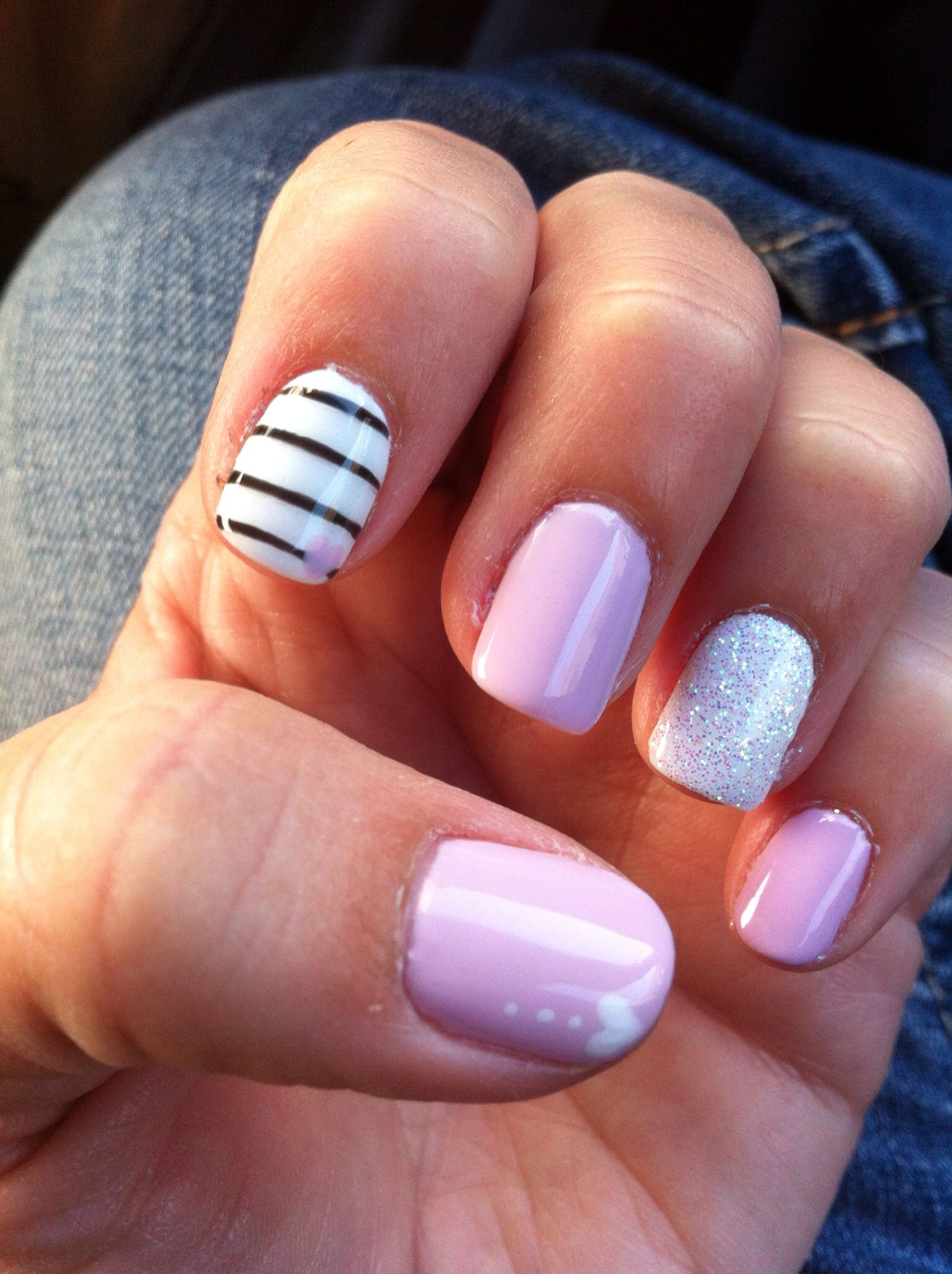 Pink and white nails, glitter ring finger, hearts, and stripes
