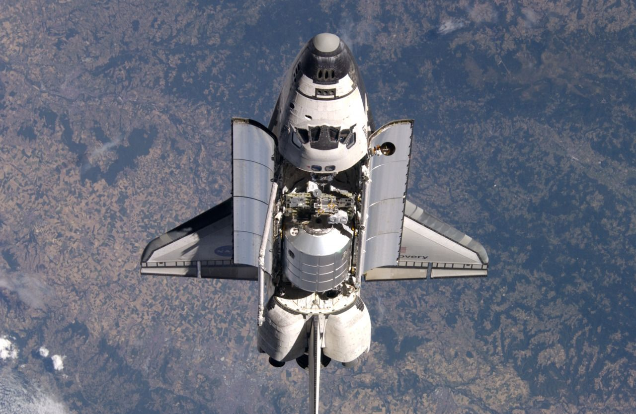 July 28, 2005 – Prior to docking with the International Space Station, the Space Shuttle Discovery performs maneuvers so that the crew on the ISS can take photographs for inspection.