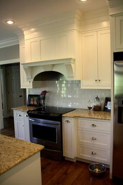 White kitchen with subway tile and a gorgeous range hood with