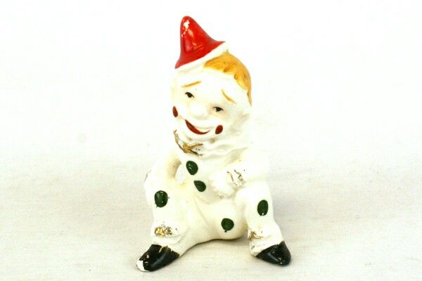 "This is a vintage porcelain clown figurine from Japan. This clown is wearing a red cap with a white suit with green polka dots and black shoes. Around the collar, sleeves and pant cuffs is gold guild. This figurine has paint wear, but is in good condition and measures 3.75"" tall and 2.5"" wide."