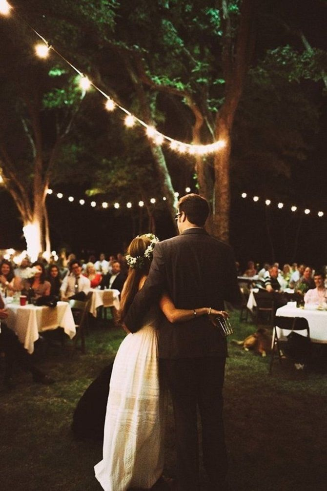 Cozy and romantic backyard wedding decor with hanging lights