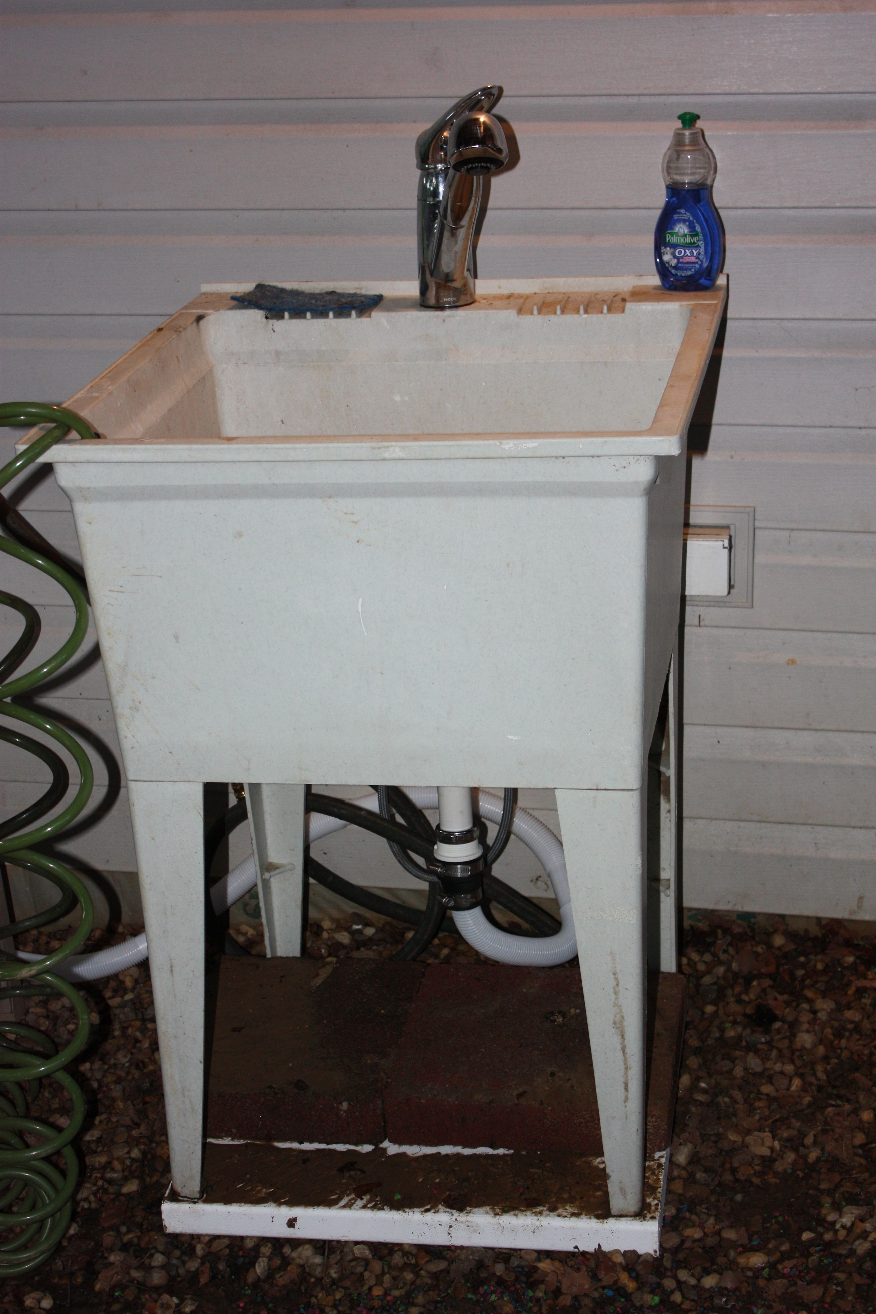 """$50 Outdoor Sink with pullout faucet. Found the sink being thrown out on the street.  Bought a Moen pullout faucet for $35 on Craigslist, a few plumbing parts to connect my hose to the cold water input of the sink, a 1 1/8"""" bilge pump hose direct to my gutter - sink installed!  Amazing how many times we use this outdoor sink!"""
