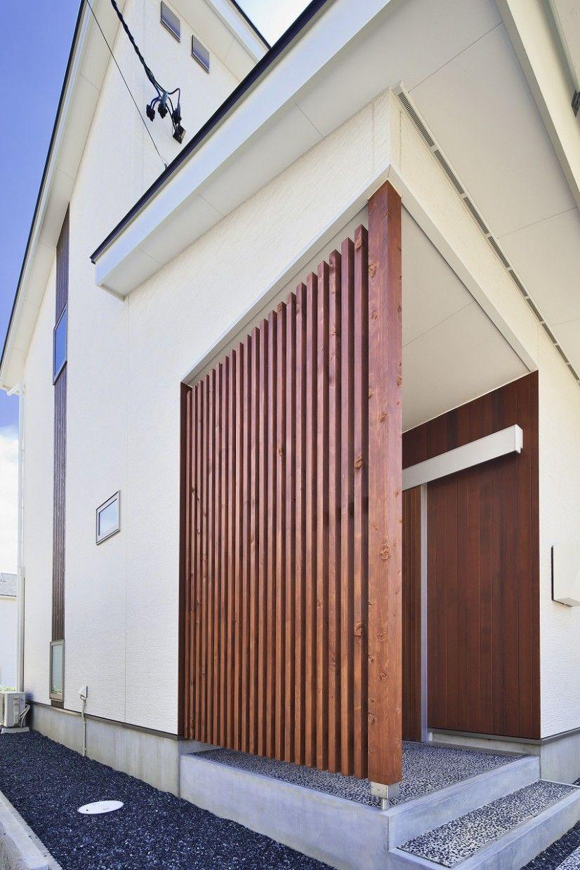 田園の中に佇む木格子が映える家 玄関 格子 玄関アプローチ タイル