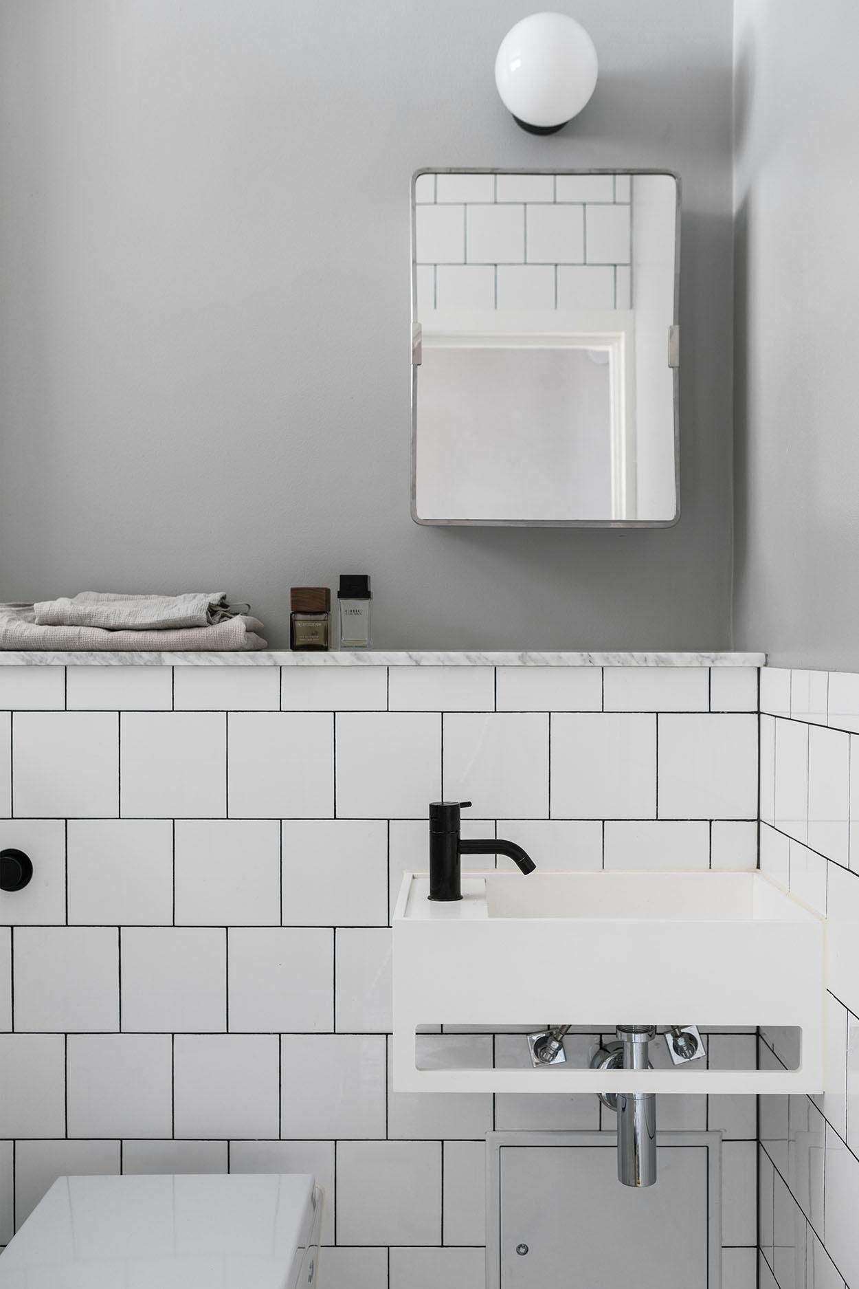 black matte tap in a white and grey bathroom. Trendy bathroom with ...