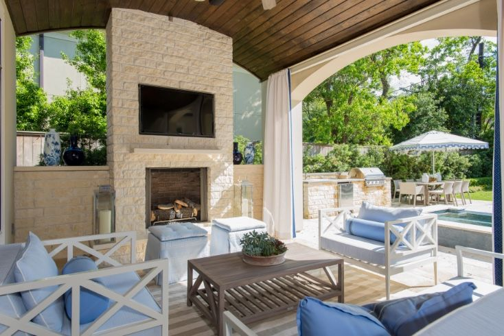 Loggia with plank barrel ceiling is filled with a brick fireplace lined with a flat panel tv niche.