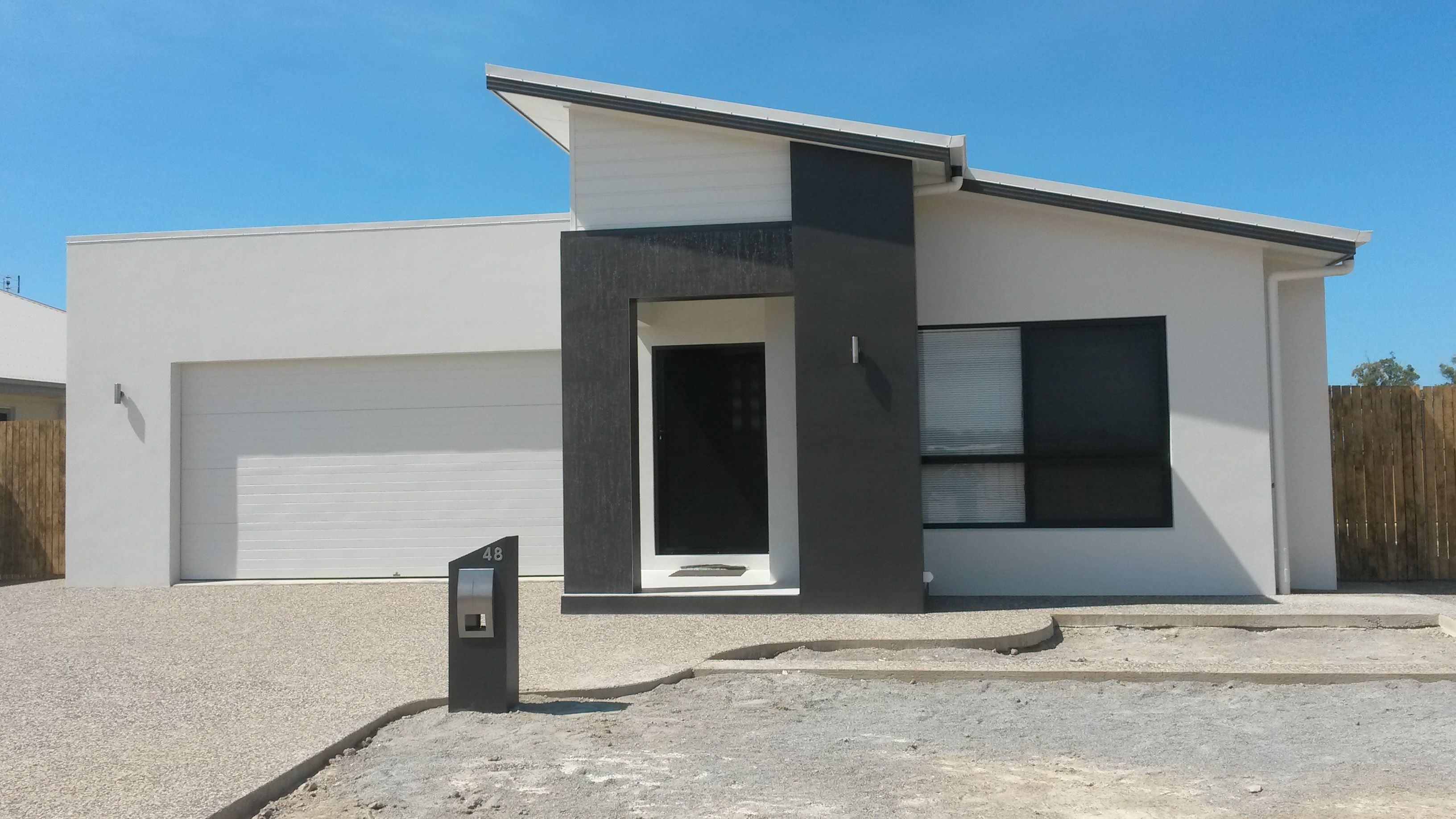 New house facade with skillion roof charcoal grey and white design new home by grady homes in townsville australia