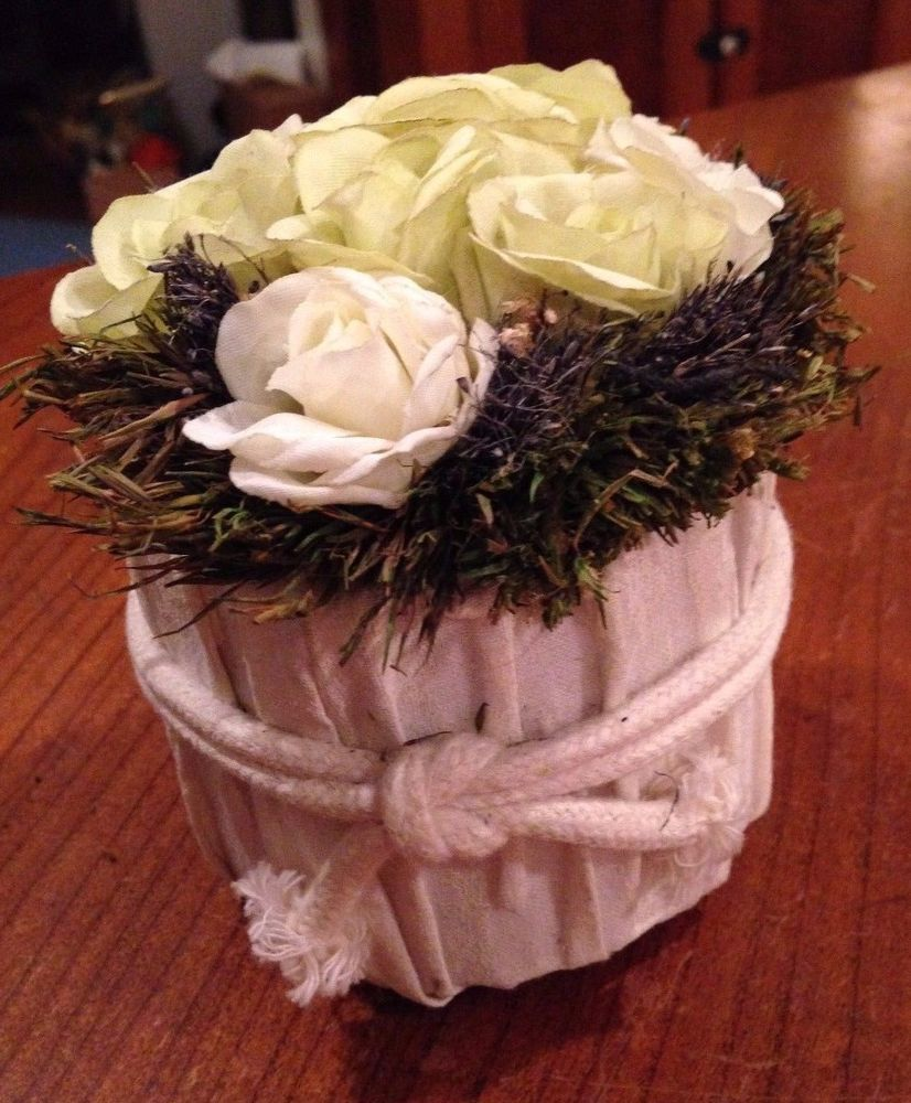 White cloth basket of white flowers with greenery