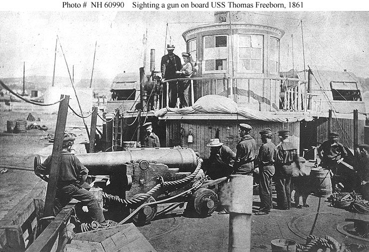 "USS Thomas Freeborn (1861-1865)  Some of the ship's officers and men demonstrate how her late Commanding Officer, Commander James H. Ward, was sighting her bow gun when he was mortally wounded on 27 June 1861, during an action with Confederate forces at Mathias Point, Virginia. The gun is a 32 pounder smoothbore, of 60 hundredweight, on a ""Novelty Carriage"". This mounting was developed by Commander Ward before the Civil War. Location appears to be the Washington Navy Yard, D.C."