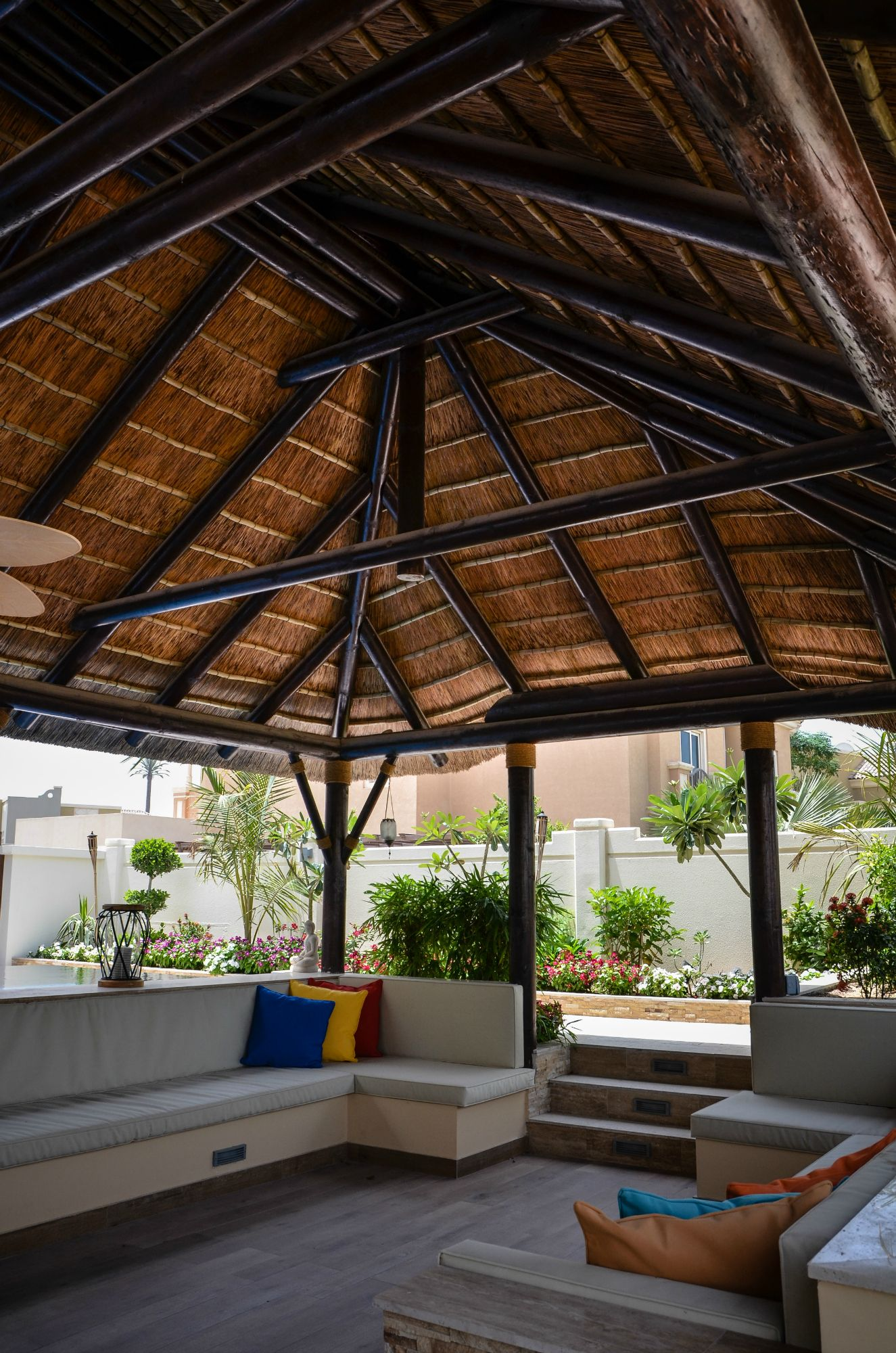 A beautifully thatched roof covers a plush seating corner and outdoor kitchen dining area perfect for alfresco dining or relaxing next to the pool by