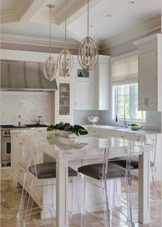 A kitchen that mixes classic and contemporary. The over all kitchen is white but the non typical vent hood adds some traditional elements while the island stools bring it into this time period. The light fixtures are a great touch and add some metallic tones to the room while the stools add some shine.
