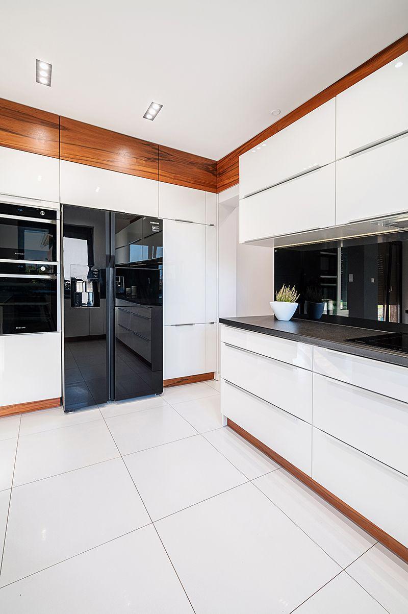 Biale Fronty Meblowe Oraz Podloga W Mlecznym Odcieniu Doskonale Podkreslaja Czarne Agd Ze Szklanym Wykonczeniem Sprawiajac Ze C Home Kitchen Cabinets Kitchen