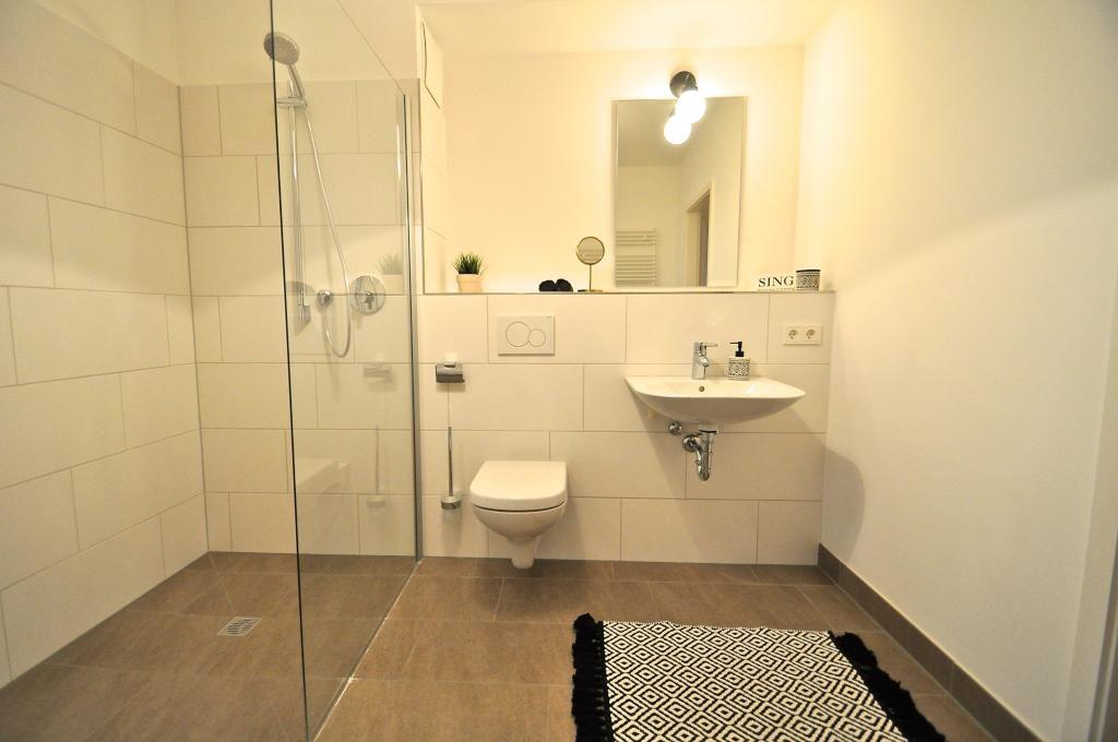 schlichtes modernes badezimmer mit ebenerdiger dusche sch nem teppich und braunem fliesenboden. Black Bedroom Furniture Sets. Home Design Ideas
