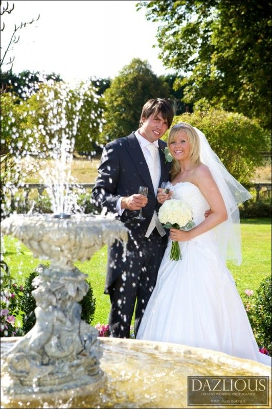 Bride and groom in front of a fountain in Essex