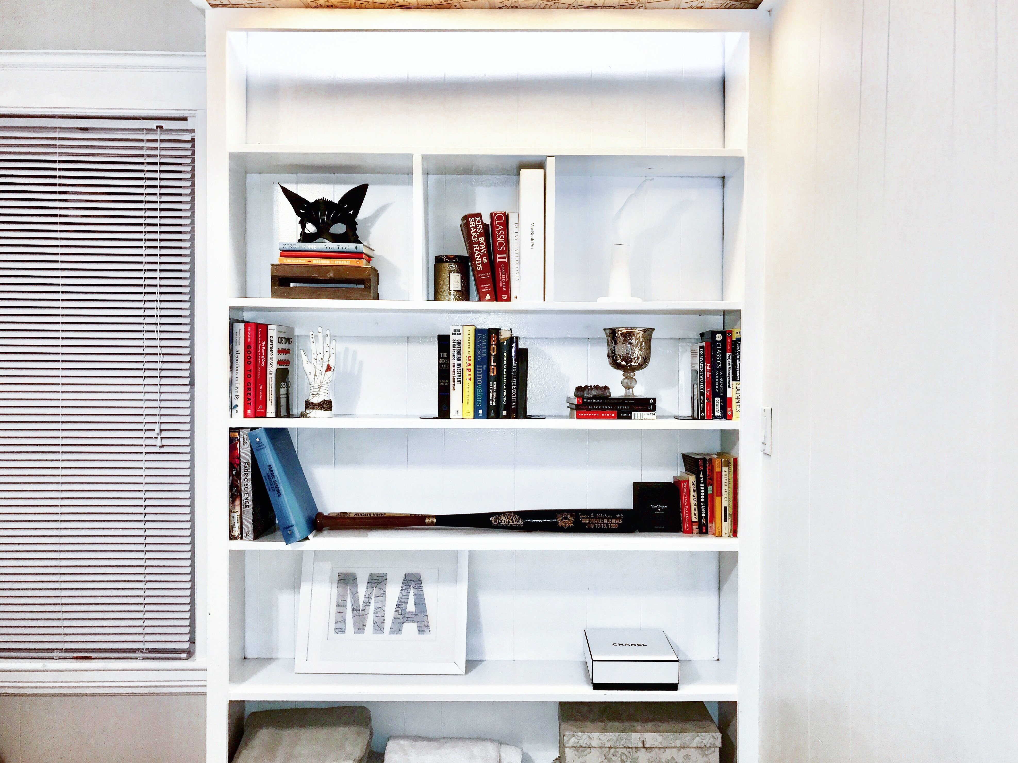 White bookshelf styling with colorful books and