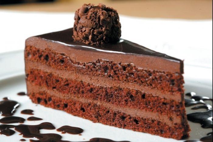Un gâteau composé de biscuit au chocolat et de couches de ganache chocolat, le tout surmonté d'un glaçage au chocolat.