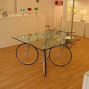 A glass top supported by a base of four-wheeled bicycle, an idea cheap, ecological and definitely original and charming.