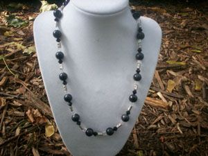 """A 19.5"""" necklace with black glass beads, black swarovski crystals, fiber optic beads, and dragonfly pillow spacers."""
