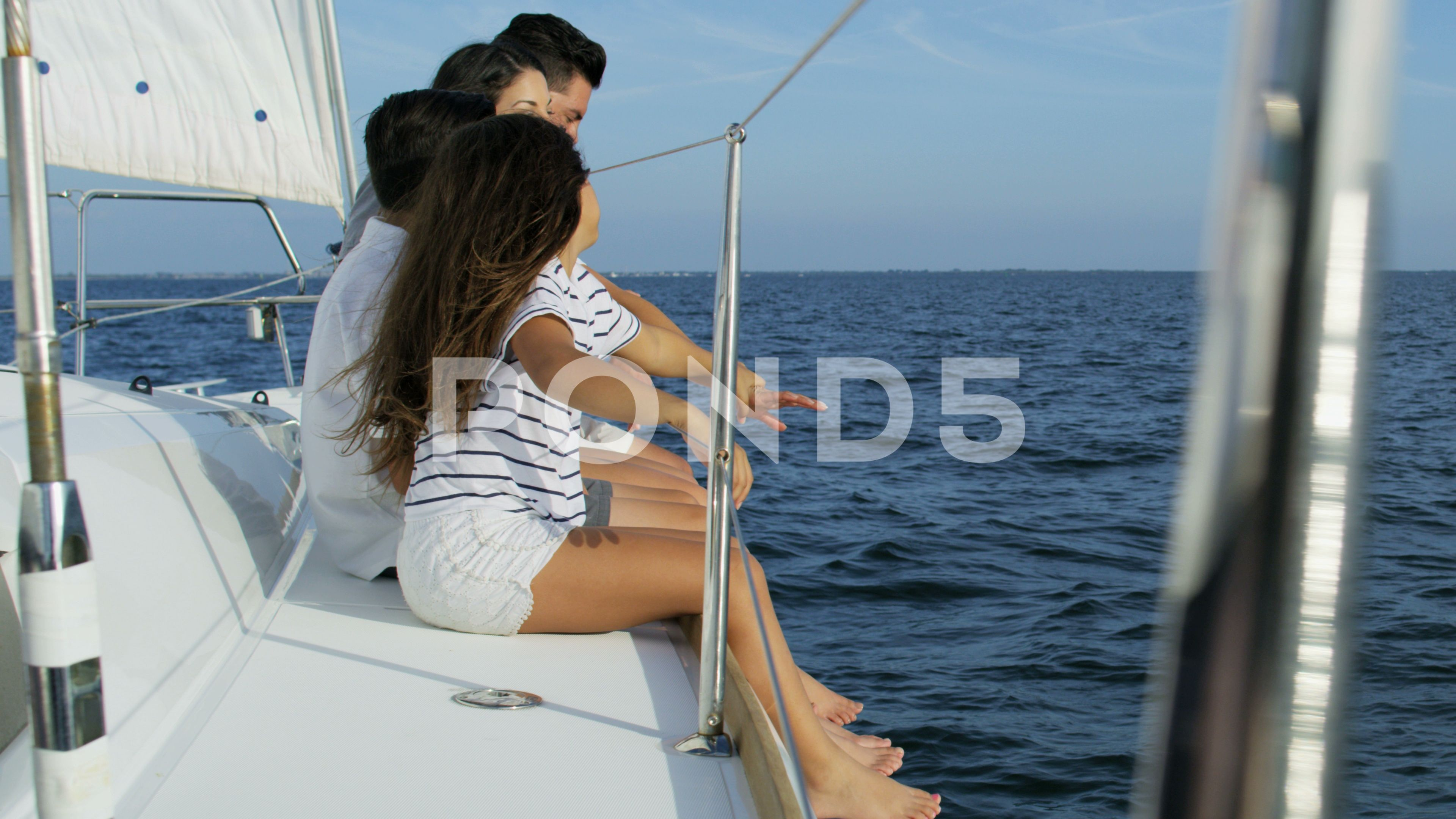 Hispanic Family In Casual Clothing At Leisure Sailing The Ocean On