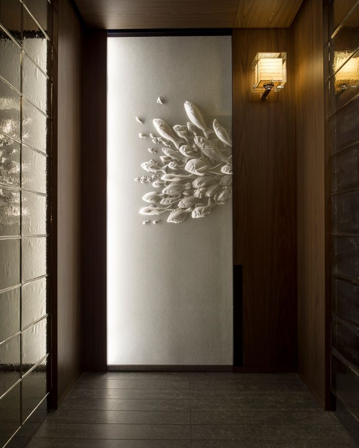 Elevator artwork incorporated within the door design. & wall grazing on textured art piece at end of corridors ...