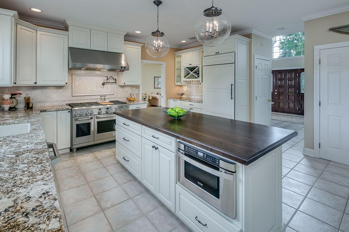 Large EIK has wood cabinetry, granite countertops, ceramic sink ...