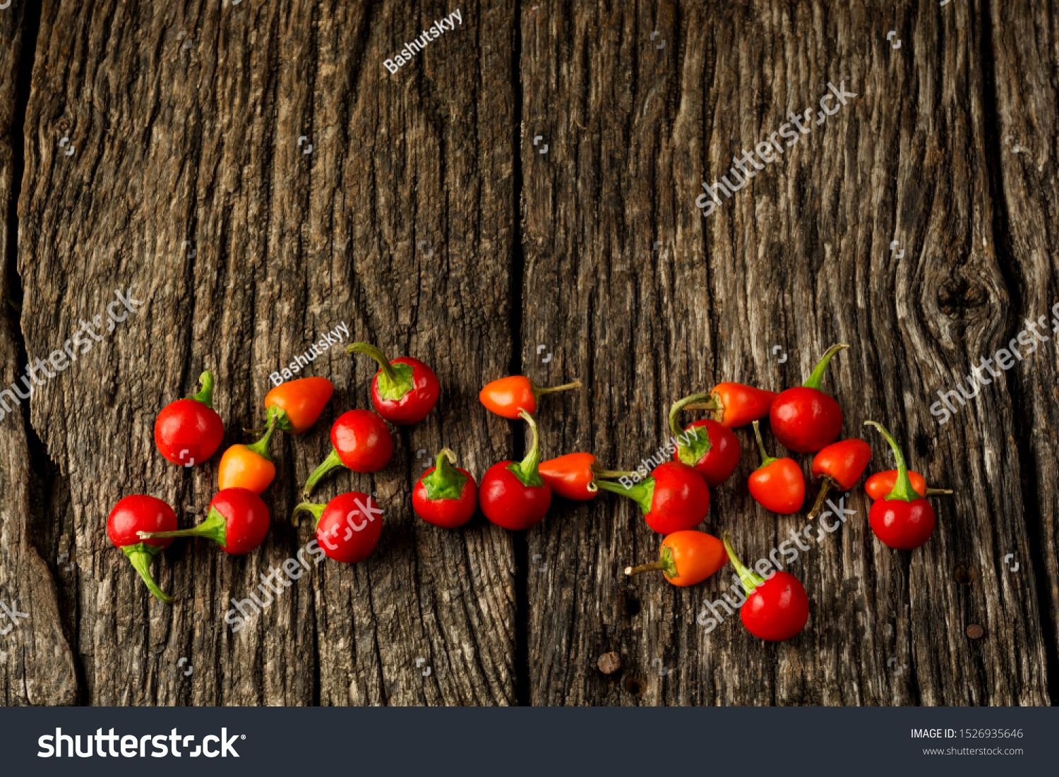 Food and drink still life concept Raw chilli peppers on a rustic wooden table Selective focus top view flat lay overhead