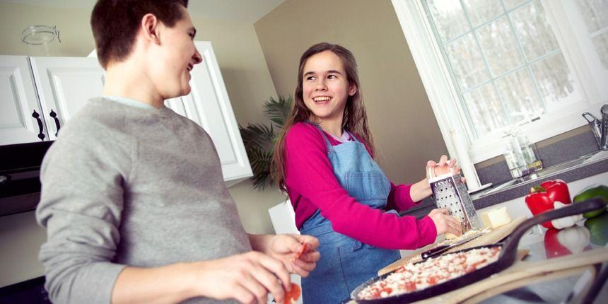 Um irmão e uma irmã fazendo pizza juntos