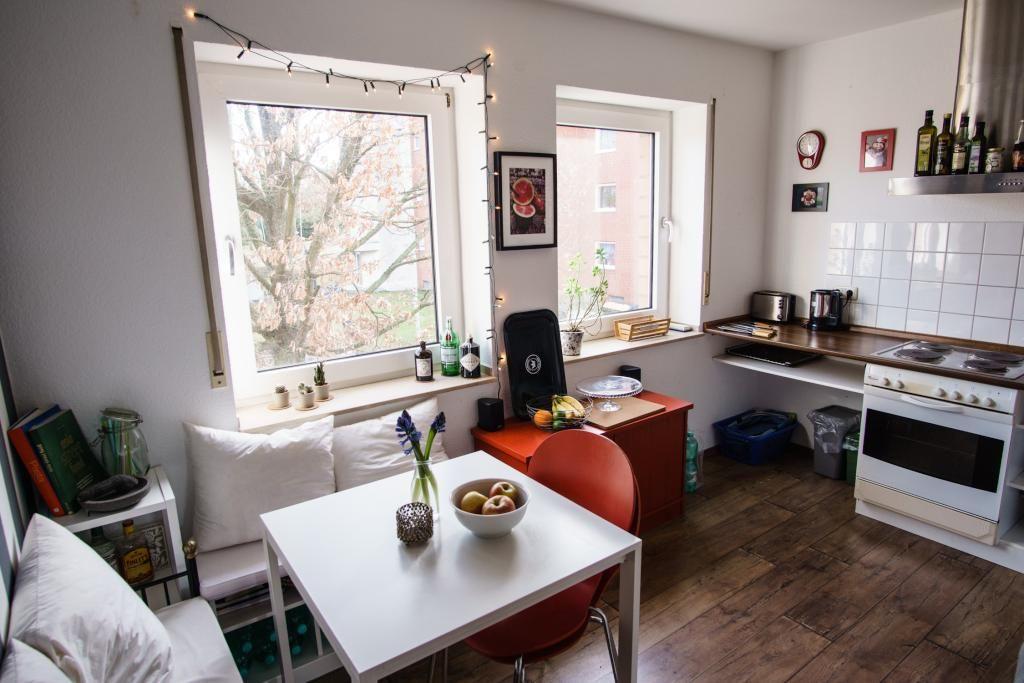 Schöne helle Küche mit Küchentisch, Sitzecke und roten Akzenten ...