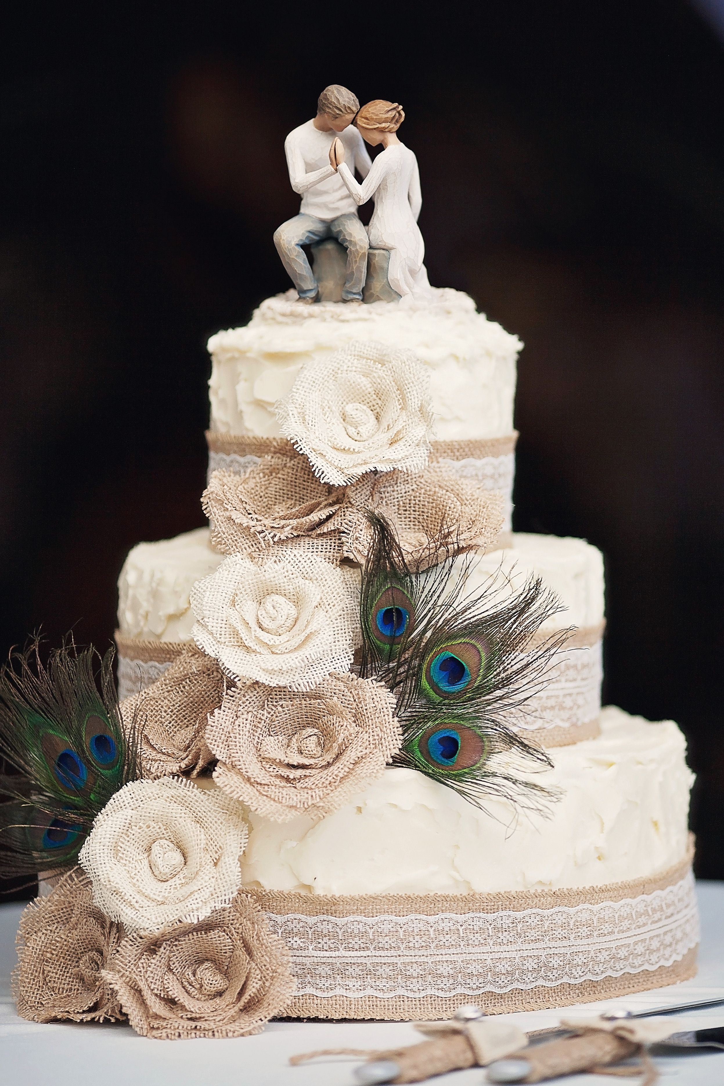 cake: burlap flowers, peacock feathers, burlap ribbon with lace